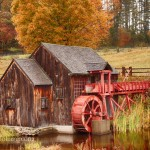 gristmill with water wheel with orange and yellow autumn fall colors