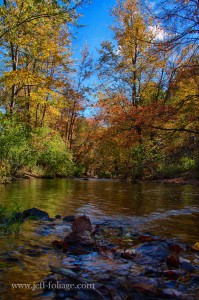 River leading up to grist mill with fall foliage reflecting on the water.