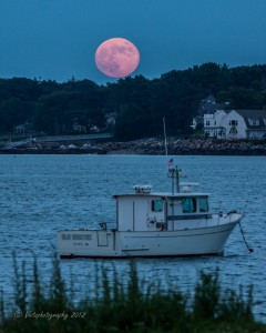 a red full moon rises over salem harbor