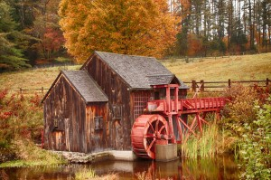 Guildhall Vermont grist mill in 1 October fall foliage an orange maple stands over the grist mill