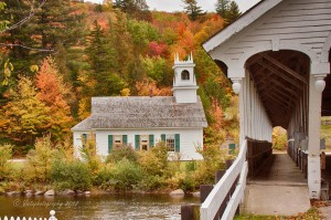 looking through the walkway of the Stark covered bridge, looking back across the river at the Stark church framed by a hillside of fall colors in Stark NH.