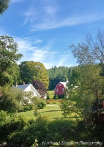 A farm house is seen in the distance with fall foliage that needs colder temps to produce the vibrant colors of autumn