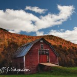 fall color covers the Hills behind the barn giving it a wonderful backdrop of fall foliage in New England and a blue sky dotted with puffy white clouds
