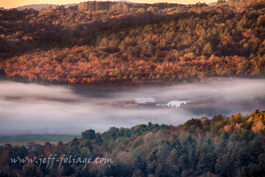 Autumn fog flows over farm and Vermont fall foliage